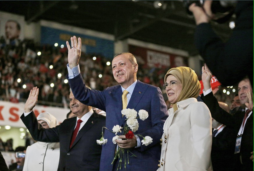 epa05978264 Turkish President Recep Tayyip Erdogan (C), his wife Emine (R) and Prime Minister Binali Yildirim (L) greet supporters of the ruling Justice and Development Party (AKP), during an extraordinary congress, in Ankara, Turkey, 21 May 2017. AKP held an extraordinary congress on 21 May where President Recep Tayyip Erdogan was expected to regain his party leadership and announce the party's new action plan for the 2019 elections, according to local media.  EPA/BURHAN OZBILICI / POOL