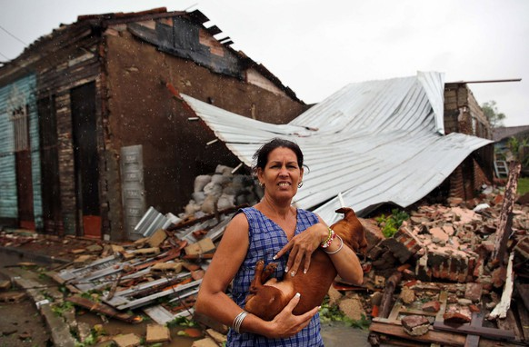 epa06195752 A woman poses with her dog in fron of her destroyed house after the Hurricane Irma, at the central city of Remedios, Cuba, 9 September 2017. The central region of Cuba woke up today in one of the most dangerous mornings of the last decades, a dawn of giant waves, hurricane winds and heavy rains caused by the fierce Irma, which has severely hit patrimonial cities like Remedios or Caibarien.  EPA/Alejandro Ernesto