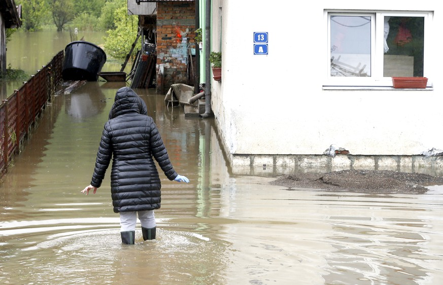 epa07570040 A woman enters a flooded house in Teslic in central Bosnia, during the floods in Bosnia and Herzegovina, 14 May 2019. The region was hit by heavy rains, causing flooding in several areas.  EPA/FEHIM DEMIR