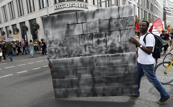 epa06021204 Two demonstrators carry a cardboard wall during a protest march against the G20-Africa Conference that takes place in Berlin next week, in Berlin, Germany, 10 June 2017. A few hundred demonstrators marched throgh the streets of the capital opposing the 'G20-Africa Partnership Conference', where various African leaders will meet with German Chancellor Angela Merkel and other politicians to discuss economic agreements. Activists criticize that Europe still plays the 'master' role and Africa remains the 'slave', with 'partnership' meaning 'economic exploitation'.  EPA/FELIPE TRUEBA