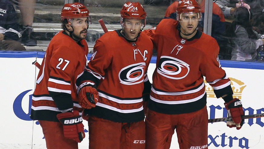 Carolina Hurricanes' Justin Williams, center, celebrates with teammates Justin Faulk (27) and Nino Niederreiter, right, after scoring a goal against the Florida Panthers during the third period of an NHL hockey game Thursday, Feb. 21, 2019, in Sunrise, Fla. The Hurricanes won 4-3. (AP Photo/Luis M. Alvarez)