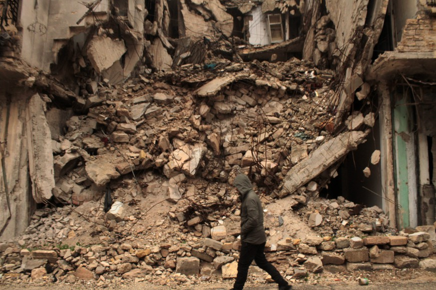 epa05675594 A man walks next to a destroyed building one day after a ceasefire was announced, at al-Mashhad neighborhood in the rebel-held part of Aleppo, Syria, 14 December 2016. Syrian Observatory for Human Rights said fighting erupted around the final rebel-held area of Aleppo on 14 December as the scheduled ceasefire and mass evacuation of opposition fighters from the area stalled.  EPA/STRINGER