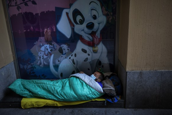 A homeless man sleeps in the doorway of a building, in Barcelona, Spain, March 15, 2020. (AP Photo/Emilio Morenatti)