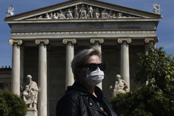 epa08293903 A woman wearing a mask waits for a bus as he stands in front of the Athens Academy building in central Athens, Greece, 14 March 2020. Greece expanded its measures of closures on Friday 13 March to prevent the spread of coronavirus epidemic by ordering the shutdown of coffee shops, bars, malls and restaurants.  EPA/YANNIS KOLESIDIS