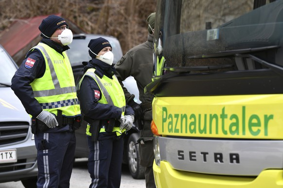 Police at a roadblock stop a bus from driving out of the Paznauntal, near Landeck, Austrian province of Tyrol, Saturday, March 14, 2020. Due to the Covid-19 virus, the towns of St. Anton am Arlberg and the Paznauntal area are isolated for 14 days. Only for most people, the new coronavirus causes only mild or moderate symptoms, such as fever and cough. For some, especially older adults and people with existing health problems, it can cause more severe illness, including pneumonia. (AP Photo/Kerstin Joensson)