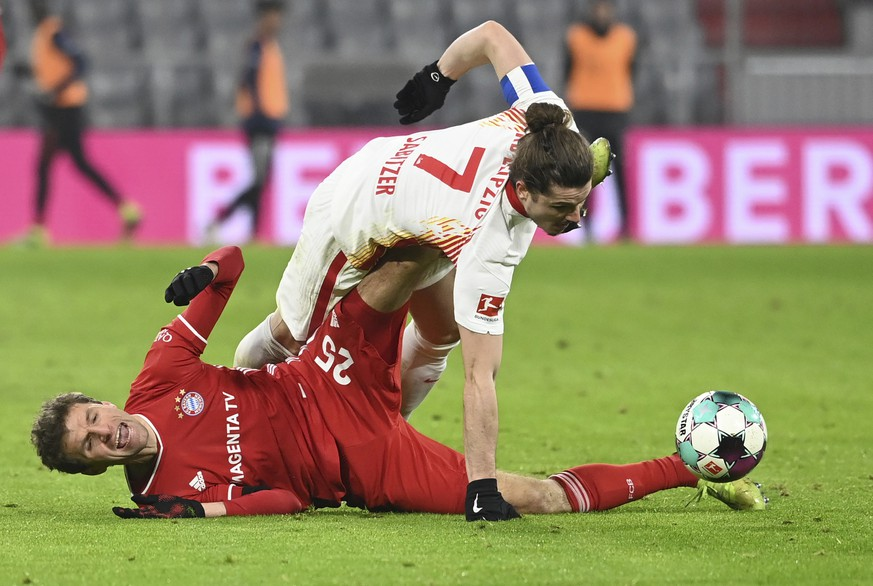 Leipzig's Marcel Sabitzer (7) and Bayern's Thomas Muller compete for the ball during a German Bundesliga soccer match between Bayern Munich and RB Leipzig in Munich, Germany, Saturday, Dec. 5, 2020. (Sven Hoppe/dpa via AP)