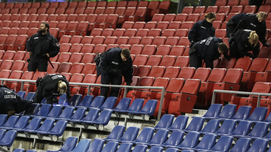 German police officers search between the seats of the stadium prior to an international friendly soccer match between Germany and the Netherlands in Hannover, Germany, Tuesday, Nov. 17, 2015.  Following the attacks in Paris, security measures have been increased for the match. (AP Photo/Markus Schreiber)