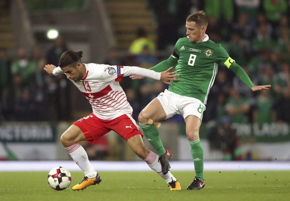 Northern Ireland's Steven Davis, right, and Switzerland's Ricardo Rodriguez battle for the ball during the World Cup qualifying play-off first leg soccer match between Northern Ireland and Switzerland at Windsor Park in Belfast, Northern Ireland, Thursday Nov. 9, 2017. (Niall Carson/PA via AP)