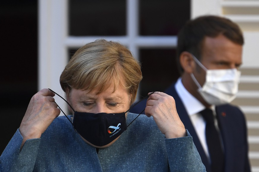 epa08614968 German Chancellor Angela Merkel wears a face mask as she arrives with French president Emmanuel Macron for a press conference after a meeting at Fort de Bregancon, in Bormes-les-Mimosas, south-east of France, 20 August 2020. French President Emmanuel Macron meets German Chancellor Angela Merkel to try to strengthen the understanding of the Franco-German couple on the many hot European and international issues.  EPA/CHRISTOPHE SIMON / POOL  MAXPPP OUT