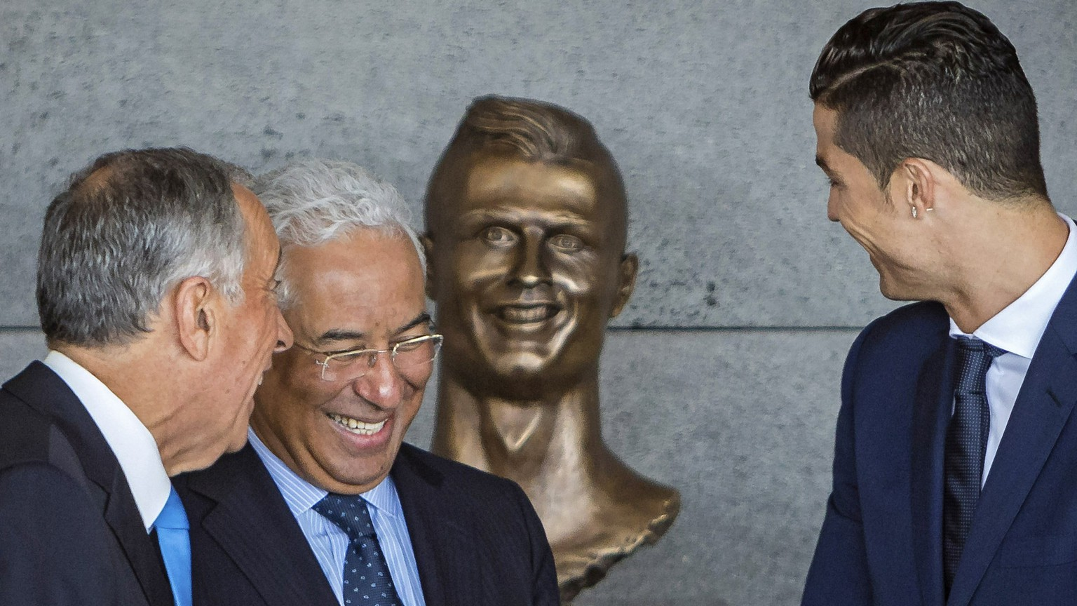 epa05877458 (L-R) Portuguese President Marcelo Rebelo de Sousa, Portuguese Prime Minister Antonio Costa, and Portuguese soccer player Cristiano Ronaldo share a light moment in front of a Ronaldo bust during a naming event at Madeira's airport in Santa Cruz, Madeira island, Portugal, 29 March 2017. The Madeira International Airport was offically named to Cristiano Ronaldo Airport in honour to Cristiano Ronaldo who was born and raised on Madeira.  EPA/GREGORIO CUNHA