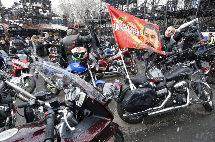 A man adjusts a flag before a farewell ceremony to see off participants of a bike ride, commemorating the 70th anniversary of the victory over Nazi Germany in World War Two, at a bike centre in Moscow, April 25, 2015. Poland will not allow members of a Russian motorcycle club linked to President Vladimir Putin to cross its border and enter the European Union's territory, the Polish Foreign Ministry said on Friday, in a decision Moscow said was politically motivated. Some 50 members of the Night Wolves, a group blacklisted by the United States for taking part in Russia's annexation of Crimea, are taking part in a bike ride from Moscow to Berlin, commemorating the 70th anniversary of the end of World War Two. The flag shows a portrait of Soviet leader Joseph Stalin and reads,