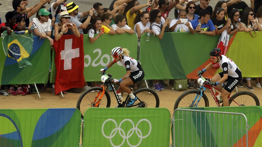 Jolanda Neff, left, and Linda Indergand, both of Switzerland, compete at the start of the women's cross-country mountain bike race at the 2016 Summer Olympics in Rio de Janeiro, Brazil, Saturday, Aug. 20, 2016. (AP Photo/Victor R. Caivano)