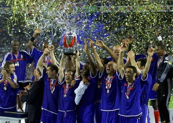 French soccer team captain Didier Deschamps, center, holds aloft the EURO 2000 Soccer Championships trophy after his team beat Italy 2-1 with a golden goal winner in extra time in the final at the De Kuip Stadium in Rotterdam, The Netherlands Sunday July 2, 2000. (AP Photo/Thomas Kienzle)