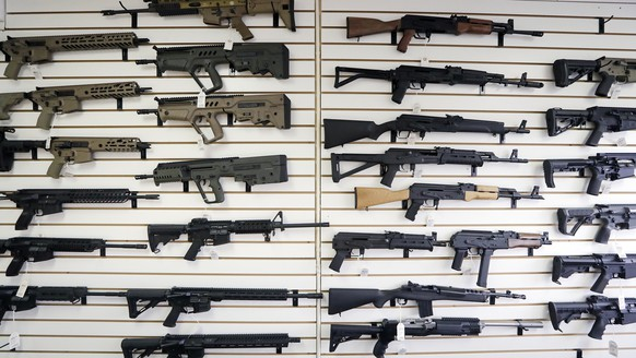 In this Oct. 2, 2018, semi-automatic rifles fill a wall at a gun shop in Lynnwood, Wash. Starting Tuesday, Jan. 1, 2019, no one under the age of 21 in Washington state will be allowed to purchase a