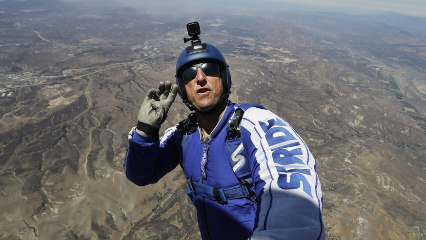 In this Monday, July 25, 2016 photo, skydiver Luke Aikins signals to pilot Aaron Fitzgerald as he prepares to jump from a helicopter in Simi Valley, Calif. After months of training, this elite skydiver says he's ready to leave his chute in the plane when he bails out 25,000 feet over Simi Valley on Saturday. That's right, no parachute, no wingsuit and no fellow skydiver with an extra one to hand him in mid-air. (AP Photo/Jae C. Hong)