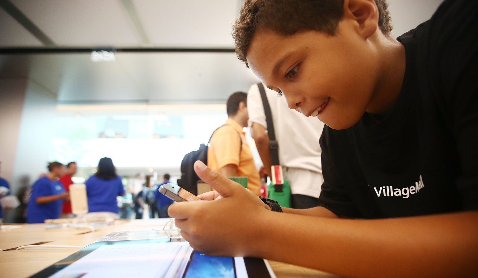 RIO DE JANEIRO, BRAZIL - FEBRUARY 15:  A boy plays with an iPhone in Brazil's first Apple retail store minutes after it opened to the public for the first time in the Village Mall shopping center on February 15, 2014 in Rio de Janeiro, Brazil. The store is a 'pavilion' design with a 100-foot curved glass panel in front and opens to the public four months before the 2014 FIFA World Cup. It is Apple's first physical store in South America.  (Photo by Mario Tama/Getty Images)