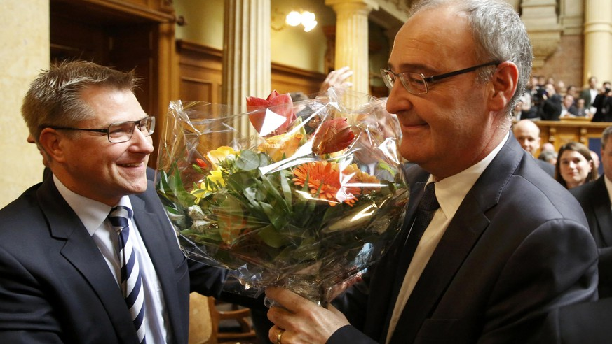 Swiss People's Party (SVP) President Toni Brunner (L) congratulates newly elected Federal Councillor Guy Parmelin (L) during the ministerial elections in the Swiss Parliament during the winter session in Bern, Switzerland December 9, 2015. REUTERS/Ruben Sprich