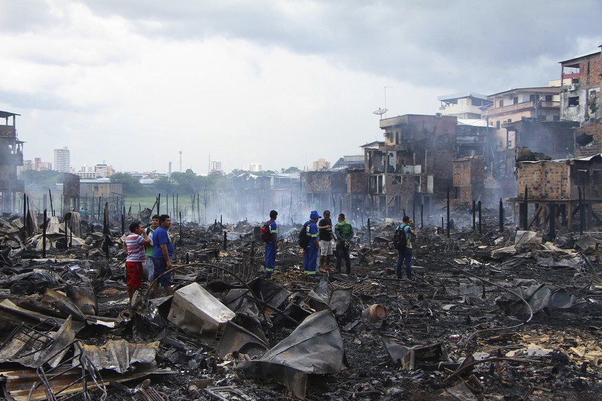 Residents stand in the scorched remains of the Educandos neighborhood in Manaus, Brazil, Tuesday, Dec. 18, 2018. Officials say the fire engulfed the neighborhood in the northern Brazilian city of Manaus and destroyed at least 600 wooden houses. (AP Photo/Edmar Barros)