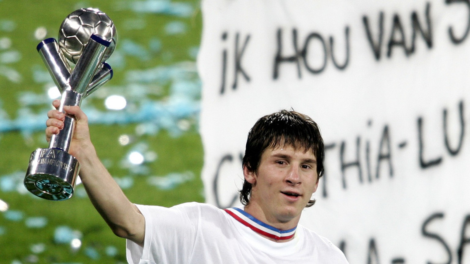 Argentina's soccer player Lionel Messi, celebrates with the trophy after Argentina beat Nigeria 2-1 during the final World Championships soccer under 20  match between Nigeria and Argentina at the Galgenwaard stadium in Utrecht, The Netherlands, Saturday July 2, 2005. Banner in the background says: Argentina I love you. (AP Photo/Bas Czerwinski)