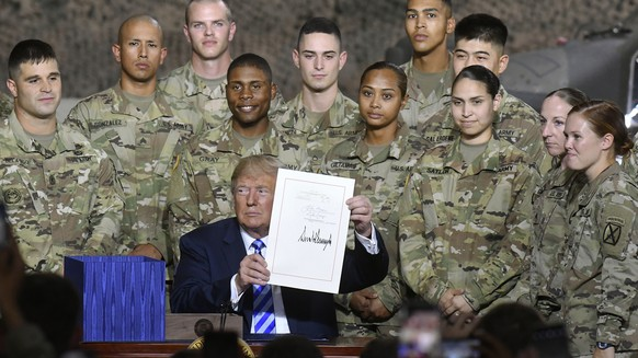 President Donald Trump holds up the $716 billion defense policy bill named for Sen. John McCain that he signed during a ceremony Monday, Aug. 13, 2018, in Fort Drum, N.Y. (AP Photo/Hans Pennink)