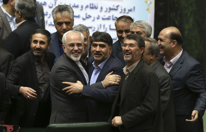 Iranian Foreign Minister Mohammad Javad Zarif, second left, who is also Iran's top nuclear negotiator is surrounded by a group of lawmakers in an open session of parliament in Tehran, Iran, Sunday, Jan. 17, 2016. Iran's President Hassan Rouhani said Sunday that the official implementation of the landmark deal reached between Tehran and six world powers has satisfied all parties except radical extremists. Rouhani said the deal has