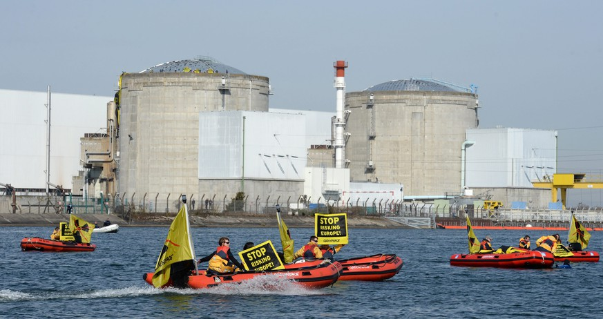 epa04130686 Greenpeace activists on rubber dinghies and holding placards with text reading 'Stop Risking Europe!' seen at the Fessenheim nuclear power plant in Fessenheim, France, 18 March 2014. An estimated 50 activists entered the grounds of the nuclear power plant. The environmental organization says it wants to draw attention to the 'danger of aging nuclear power plants in Europe'.  EPA/PATRICK SEEGER