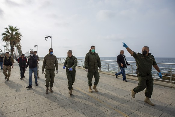 Municipal policemen order people to evacuate the corniche, or waterfront promenade, along the Mediterranean Sea, as the country's top security council and the government were meeting over the spread of coronavirus, in Beirut, Lebanon, in Beirut, Lebanon, Sunday, March 15, 2020.  Lebanon has been boosting precautionary measures including halting flights from several countries, closing all restaurants and nightclubs and tightening measures along the border with neighboring Syria. (AP Photo/Hassan Ammar)