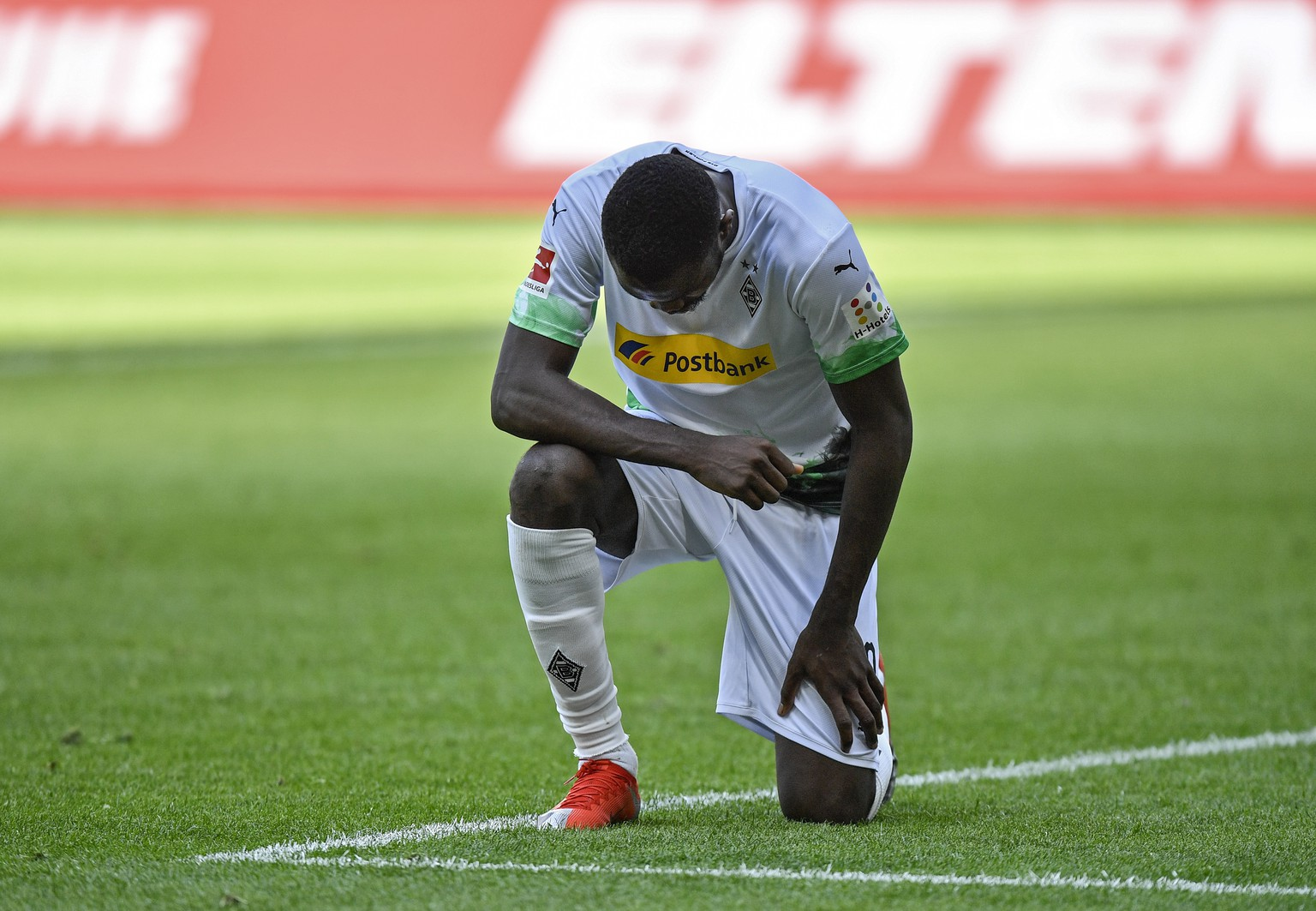 Moenchengladbach's Marcus Thuram taking the knee after scoring his side's second goal during the German Bundesliga soccer match between Borussia Moenchengladbach and Union Berlin in Moenchengladbach, Germany, Sunday, May 31, 2020. The German Bundesliga becomes the world's first major soccer league to resume after a two-month suspension because of the coronavirus pandemic. (AP Photo/Martin Meissner, Pool)