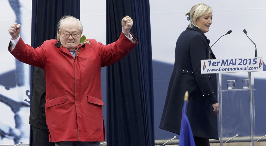 France's far-right National Front political party leader Marine Le Pen (R) walks to the lecturn as her father Jean-Marie Le Pen, party founder and honorary president, reacts on the podium at their traditional May Day tribute to Joan of Arc in Paris, France, May 1, 2015.   REUTERS/Philippe Wojazer