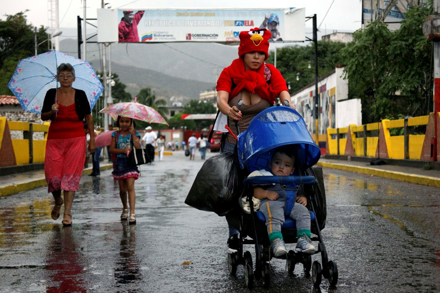 A woman push a pram with a baby and bags as she crosses the Colombian-Venezuelan border over the Simon Bolivar international bridge after shopping, in San Antonio del Tachira, Venezuela, July 16, 2016. REUTERS/Carlos Eduardo Ramirez