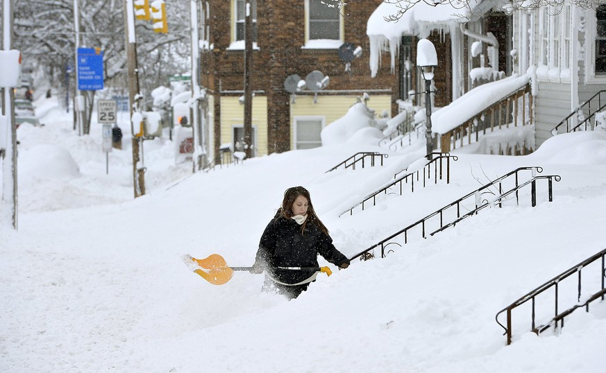 Rochelle Carlotti, 28, shovels steps near her home after a record snowfall on Tuesday, Dec. 26, 2017, in Erie, Pa. The National Weather Service office in Cleveland says Monday's storm brought 34 inches of snow, an all-time daily snowfall record for Erie. (Greg Wohlford/Erie Times-News via AP)