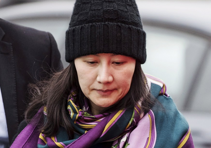 FILE - In this Dec. 12, 2018, file photo, Huawei chief financial officer Meng Wanzhou arrives at a parole office with a security guard in Vancouver, British Columbia. Canada arrested Meng at America's request on a stopover at Vancouver airport. The U.S. is reportedly investigating Huawei's use of a Hong Kong shell company to sell equipment to Iran in violation of U.S. sanctions. The United States has brought charges against Chinese tech giant Huawei Technologies and one of its top executives in a case that has shaken China's relations with the U.S. and Canada. (Darryl Dyck/The Canadian Press via AP, File)