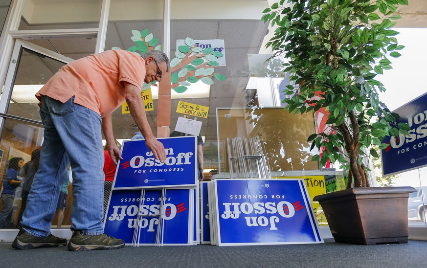 epa05906371 Campaign volunteer Richard Hughes organizes yard signs for Democratic US House of Representatives candidate Jon Ossoff at a campaign office in Chamblee, Georgia, USA, 13 April 2017. Ossoff is one of 18 candidates running in the non-partisan special election to fill Georgia's Sixth Congressional District seat previously held by Health and Human Services Secretary Tom Price, a Republican.  EPA/ERIK S. LESSER