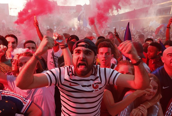 epa06878899 French supporters celebrate their team's first goal as they watch the FIFA World Cup 2018 semi final match between France and Belgium at a public viewing in Montpellier, southern France, 10 July 2018.  EPA/GUILLAUME HORCAJUELO