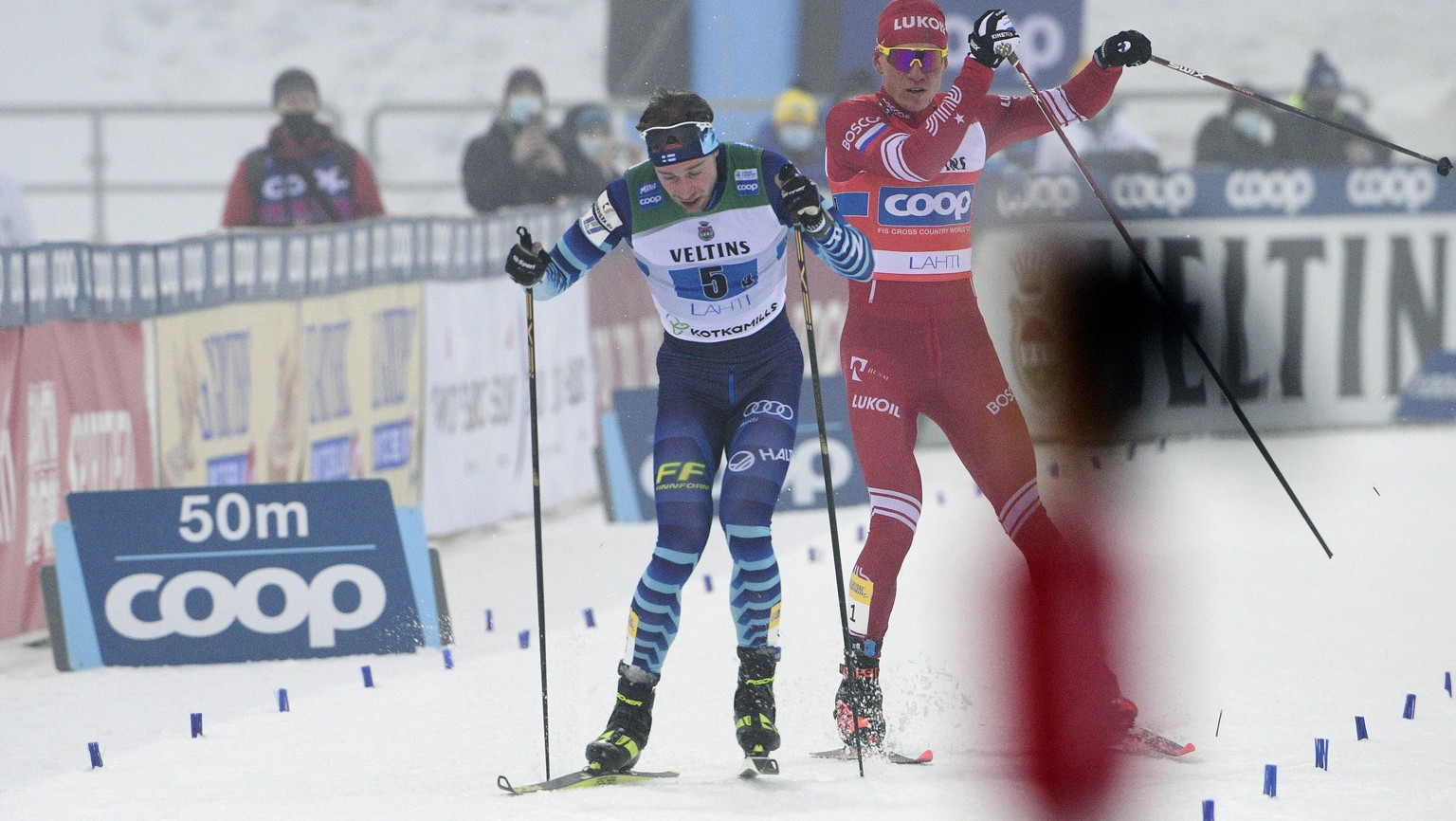 Russia's Alexander Bolshunov, right, and Joni Maki of Finland during the final meters of the men's Cross Country relay 4 x 7.5km at the FIS World Cup Lahti Ski Games in Lahti, Finland, Sunday Jan. 24, 2021. (Markku Ulander/Lehtikuva via AP)