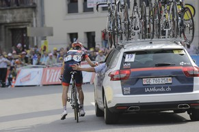 A team car pushes Switzerland's Mathias Frank to the finish after he crashed during the seventh stage of the Tour de France cycling race over 234.5 kilometers (145.7 miles) with start in Epernay and finish in Nancy, France, Friday, July 11, 2014. (AP Photo/Laurent Cipriani)