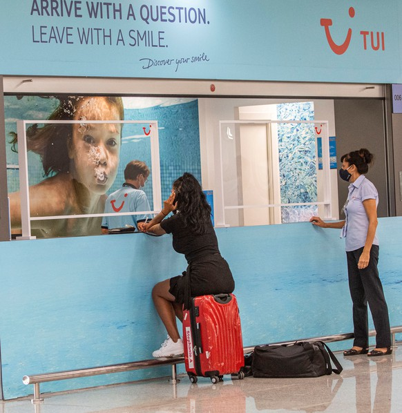 epa08605626 A traveler with her baggage waits next to a stand of TUI travel company at Palma de Mallorca's Airport in Palma, Balearic Islands, Spain, 15 August 2020. German traveler company TUI  on 15 August has canceled all its flights to Spain, including Balearic Islands and excepting Canary Islands, after the recommendation of German government due to the high number of new coronavirus cases in the country. TUI announced the cancellation of the Spanish flights from 15 to 24 August 2020.  EPA/CATI CLADERA