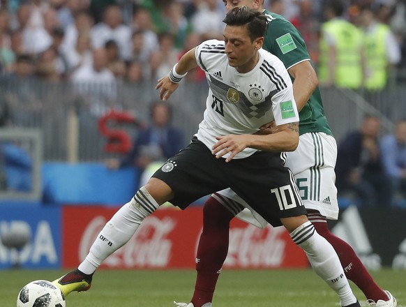 epa06816360 Mesut Oezil (front) of Germany and Hector Herrera of Mexico in action during the FIFA World Cup 2018 group F preliminary round soccer match between Germany and Mexico in Moscow, Russia, 17 June 2018.  (RESTRICTIONS APPLY: Editorial Use Only, not used in association with any commercial entity - Images must not be used in any form of alert service or push service of any kind including via mobile alert services, downloads to mobile devices or MMS messaging - Images must appear as still images and must not emulate match action video footage - No alteration is made to, and no text or image is superimposed over, any published image which: (a) intentionally obscures or removes a sponsor identification image; or (b) adds or overlays the commercial identification of any third party which is not officially associated with the FIFA World Cup)  EPA/SERGEI ILNITSKY   EDITORIAL USE ONLY