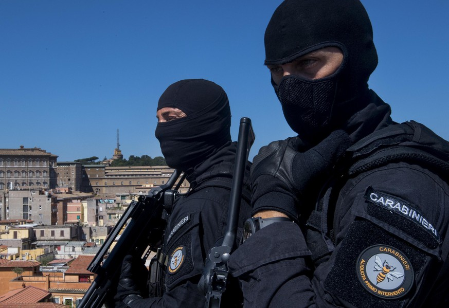 FILE - In this Tuesday, Aug. 9, 2016 file photo, Carabinieri (Italian paramilitary police) special unit's officers patrol the area next to St. Peter's Basilica, background left, in Rome. For many of the poor and destitute whom Mother Teresa served, the tiny nun was a living saint. Many at the Vatican would agree, but the Catholic Church nevertheless has a grueling process to make it official, involving volumes of historical research, the hunt for miracles and teams of experts to weigh the evidence. In Mother Teresa's case, the process will come to a formal end Sunday, Sept. 4, 2016 when Pope Francis declares the church's newest saint. Here's a look at the process. (Claudio Peri/ANSA via AP)