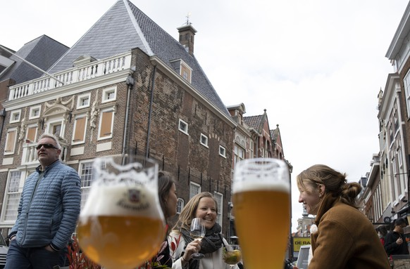 People enjoy a chilly weekend afternoon on a terrace in Haarlem, Netherlands, Saturday, May 1, 2021. The Netherlands became the latest European country to begin cautiously relaxing its lockdown even as infection rates and intensive care occupancy remain stubbornly high. The Dutch follow Italy, Greece, France and other European nations in moving to reopen society and edge away from economically crippling lockdowns in the coming weeks. (AP Photo/Peter Dejong)