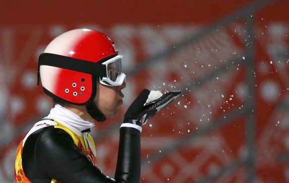 Switzerland's Simon Ammann blows snow after his jump during the final round of the men's ski jumping large hill individual final of the Sochi 2014 Winter Olympic Games, at the RusSki Gorki Ski Jumping Center in Rosa Khutor, February 15, 2014.                  REUTERS/Michael Dalder (RUSSIA  - Tags: OLYMPICS SPORT SKIING TPX IMAGES OF THE DAY)