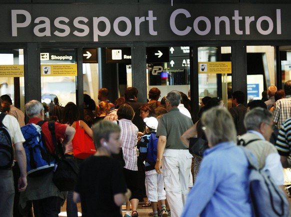 Flight passengers line up in front of the passport control, at the Zurich Airport in Kloten, Switzerland, Friday, July 11, 2008, at the beginning of the summer holidays period in many parts of Switzerland. (KEYSTONE/Steffen Schmidt)