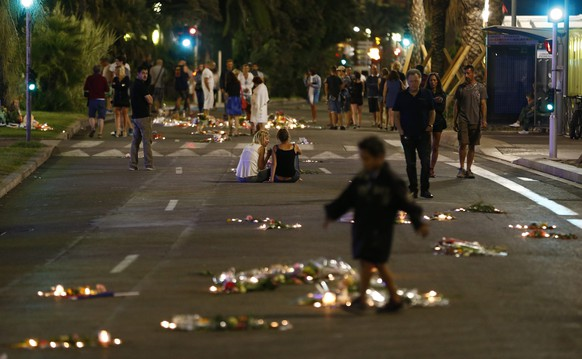epa05428725 People walk past flowers and candles on the 'Promenade des Anglais' where the truck crashed into the crowd during the Bastille Day celebrations, in Nice, France, 17 July 2016. According to reports, at least 84 people died and many were wounded after a truck drove into the crowd on the famous Promenade des Anglais during celebrations of Bastille Day in Nice, late 14 July.  EPA/IAN LANGSDON