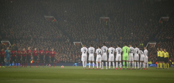 Manchester United and Paris Saint Germain line up as they applaud the memory of former England goalkeeper Gordon Banks who has died, before the start of the Champions League round of 16 soccer match between Manchester United and Paris Saint Germain at Old Trafford stadium in Manchester, England, Tuesday, Feb. 12,2019.(AP Photo/Dave Thompson)