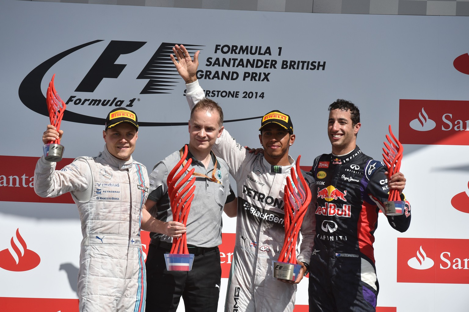 Mercedes-AMG's British driver Lewis Hamilton (2-R) celebrates on the podium along with Mercedes-AMG's German driver Nico Rosberg (L) and Red Bull Racing's Australian driver Daniel Ricciardo after winning the British Formula One Grand Prix at the Silverstone circuit in Silverstone on July 6, 2014. AFP PHOTO / DIMITAR DILKOFF