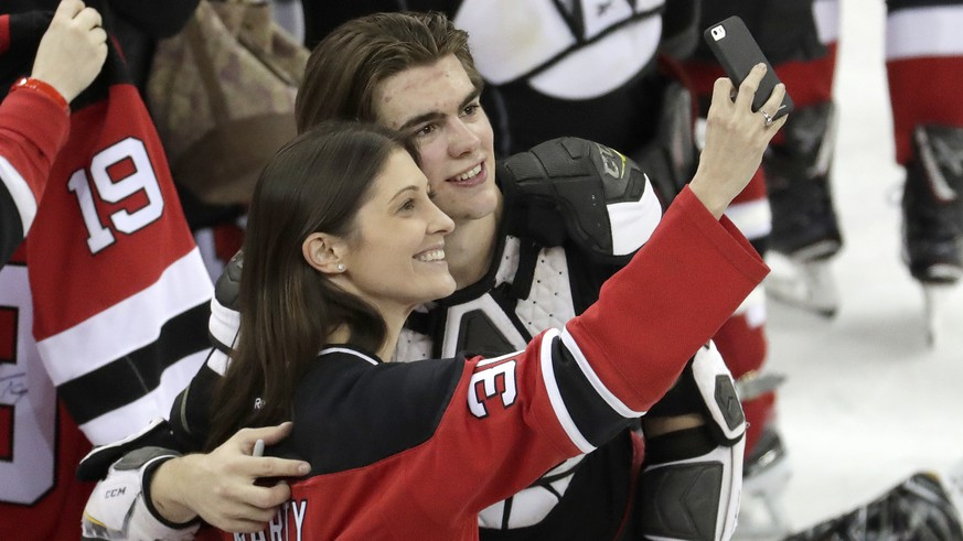 New Jersey Devils center Nico Hischier, right, of Switzerland, takes a photo with a fan after defeating the Toronto Maple Leafs in an NHL hockey game, Thursday, April 5, 2018, in Newark, N.J. (AP Photo/Julio Cortez)