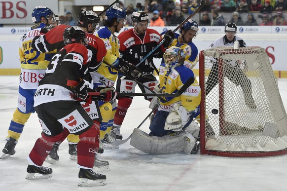 epa04540733 (L-R) Davos' Felicien du Bois, Samuel Guerra, goalkeeper Leonardo Genoni and Dino Wieser, fight for the puck against Team Canada's Derrick Walser, Marc Antoine Pouliot and Ben Walter, during the game between Switzerland's HC Davos and Team Canada at the 88th Spengler Cup ice hockey tournament in Davos, Switzerland, 26 December 2014.  EPA/PETER SCHNEIDER