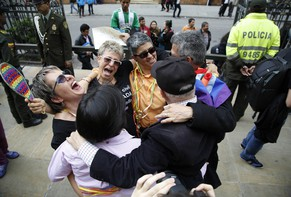 In this Thursday, April 7, 2016 photo, LGBT rights activist celebrate a Constitutional Court decision to give gay couples marriage rights, outside the Justice Palace in Bogota, Colombia. Gay couples in Colombia are already allowed to form civil unions, but the court ruled to expand rights further by giving gay couples marriage rights. (AP Photo/Fernando Vergara)