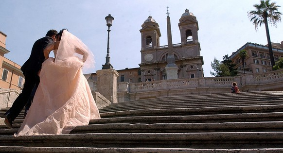 A newlywed couple walk up the unusually empty Spanish Steps, in central Rome, Saturday, July 26, 2003. According to reports, 8 million Italians are expected to leave the main cities to reach their traditional Summer resorts. (KEYSTONE/AP Photo/Gregorio Borgia)