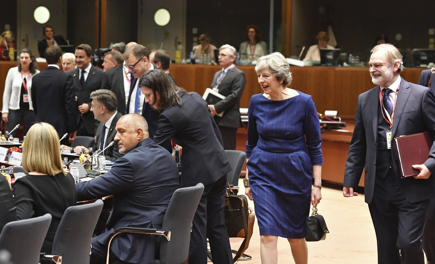 British Prime Minister Theresa May, second right, and British Ambassador to the EU Tim Barrow, right, arrive for a round table meeting at an EU summit in Brussels on Thursday, Oct. 19, 2017. British Prime Minister Theresa May headed to a European Union summit Thursday with a pledge to treat EU residents well once Britain leaves the bloc. (AP Photo/Geert Vanden Wijngaert)
